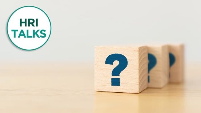 Three wooden blocks with question marks and text that says HRI Talks